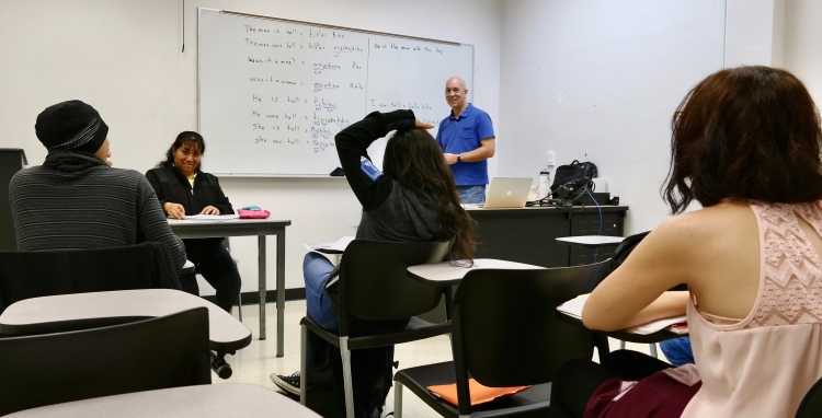 Professor John Boyles works with students and a language consultant in a field methods class.