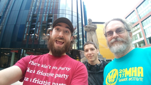 Zach Metzler, Trevor Driscoll and Dr. Chris Golston in front of a statue of Friedrich Engels in Manchester, England.