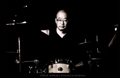 Brian Hamada sits behind his drum set (Photo courtesy of Joe Osejo Photography)
