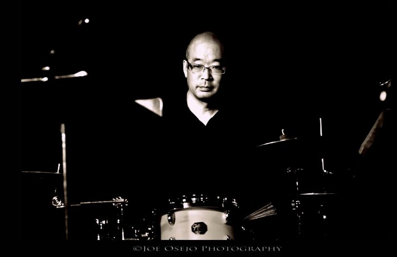 Brian Hamada sits behind his drum set (Photo courtesy of Joe Osejo Photography)