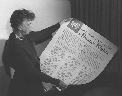 The late Eleanor Roosevelt looks at a copy of the Universal Declaration of Human Rights the day after the United Nations adopted it in 1948 to prevent and suppress genocide. Lake Success, New York, Nov. 1949, Public Domain