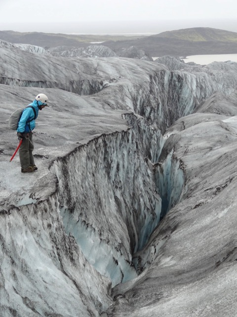 Jes Therkelsen looks down a crevasse in Iceland.