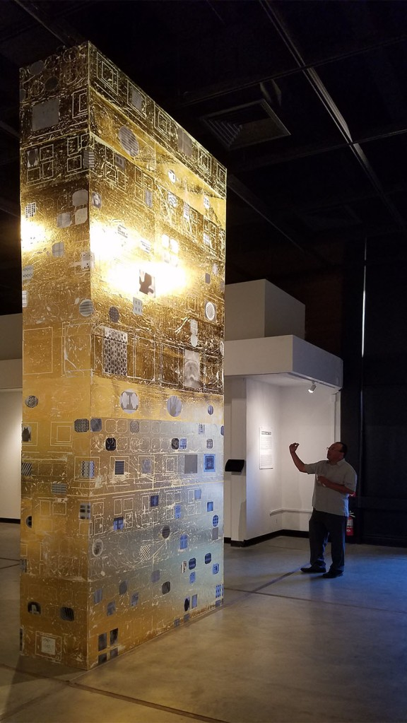 Martin Valencia, Art and Design Department Chair, takes a picture of the gold foil totem