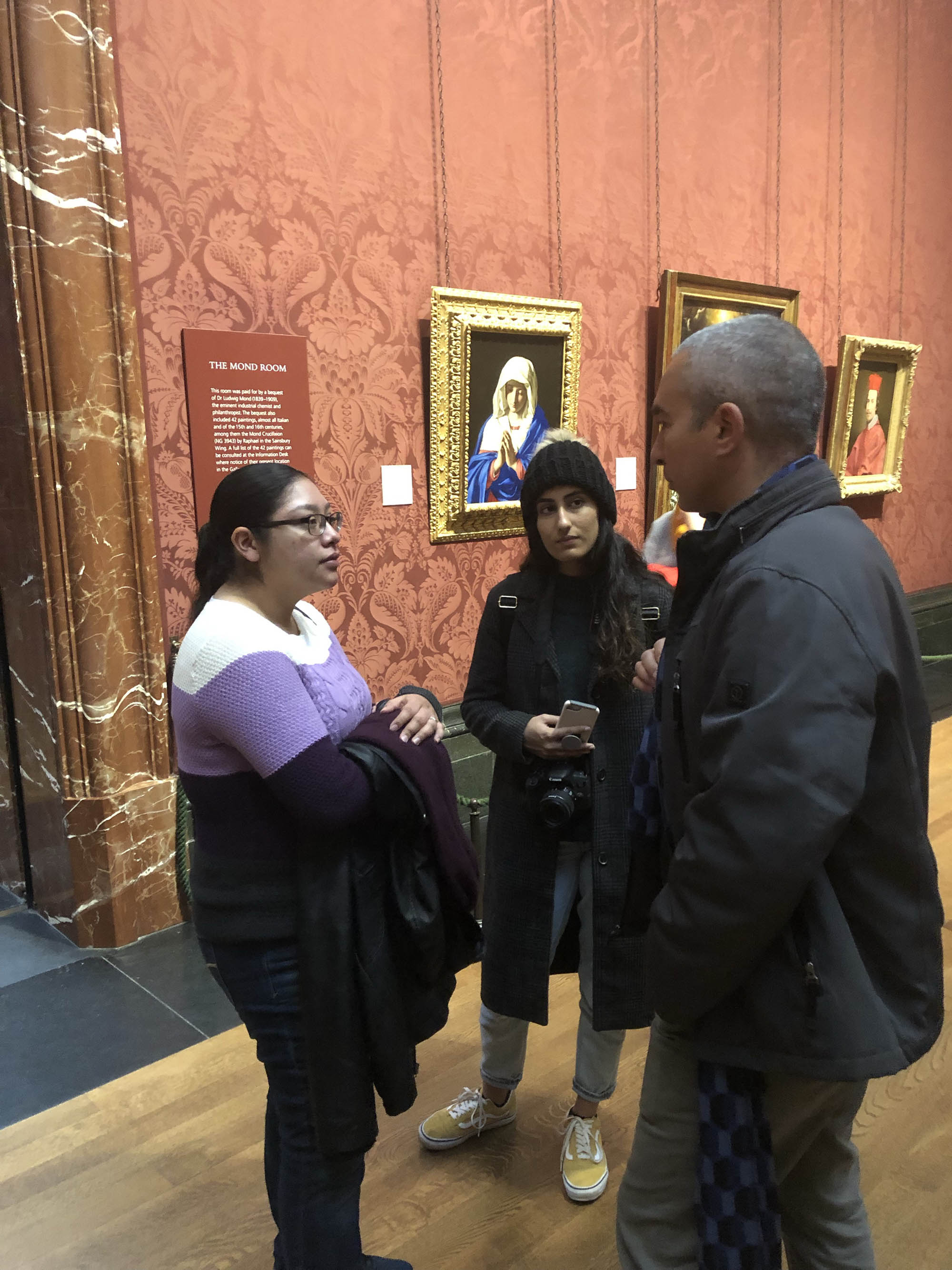 Professor Potter speaks with students about the paintings.