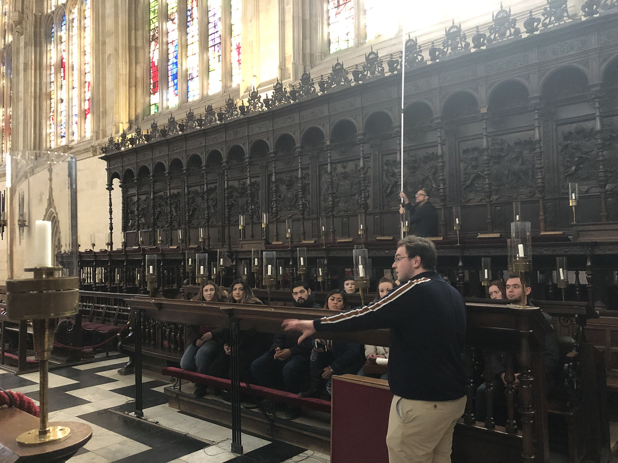 Students seated in the choir stalls at King's College Cambridge to listen about the choir at the Chapel.