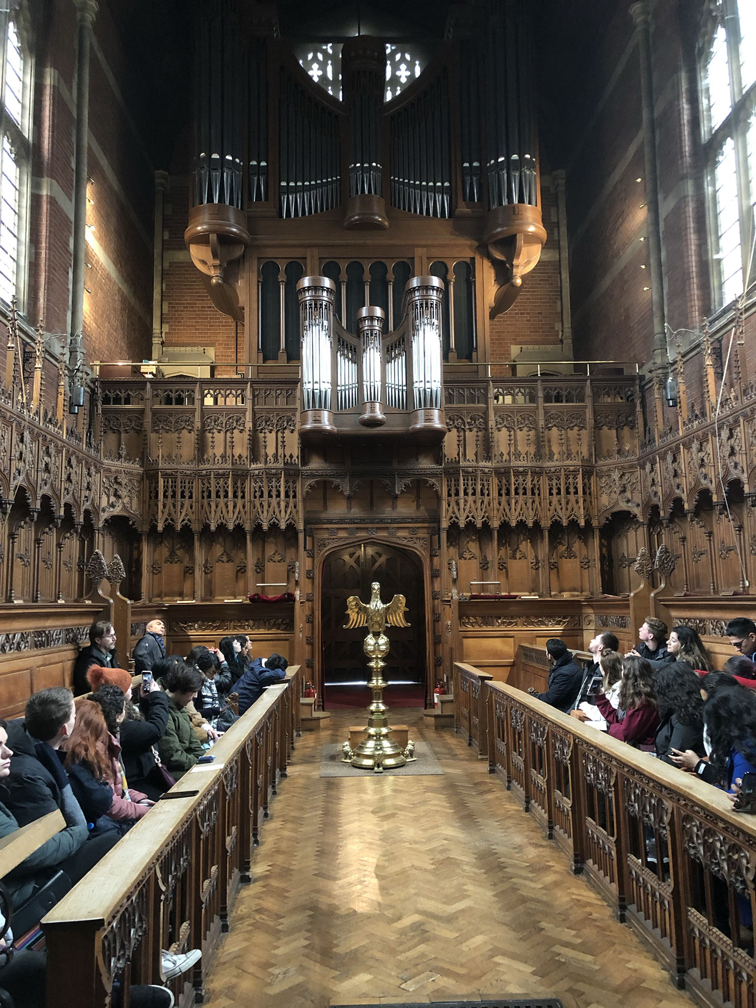 Fresno State students sit and listen to Sarah MacDonald play the organ for them in the Selwyn College Chapel.