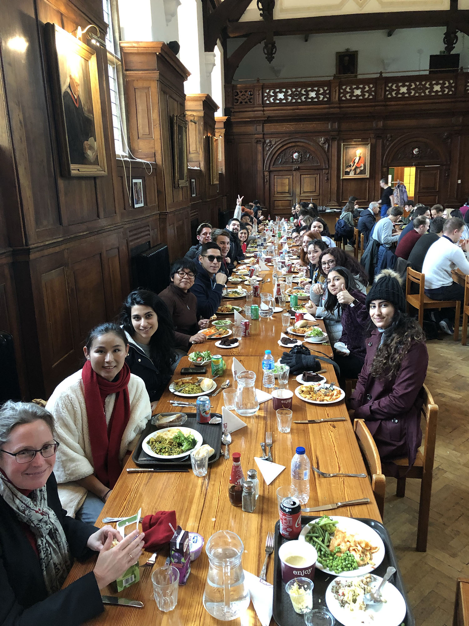 Fresno State students sit for lunch in the Selwyn College Cambridge Dining hall with Sarah MacDonald (bottom left) organist and choirmaster at Selwyn College.