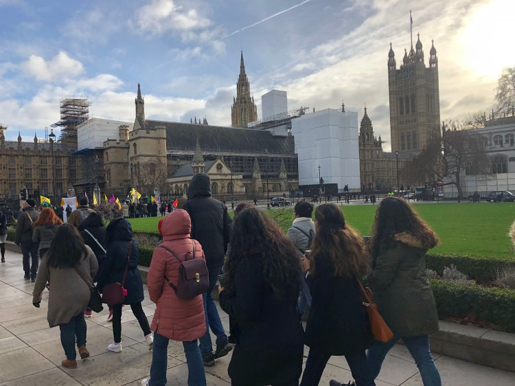 Students walk past Westminster Palace.