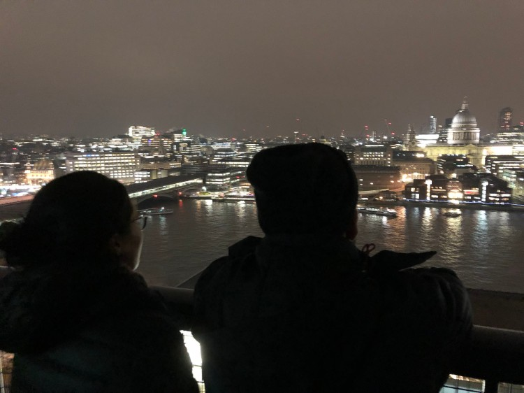 Students Victoria and Alejandro look out over the Thames at St Paul's from the top of the Tate Modern Museum.