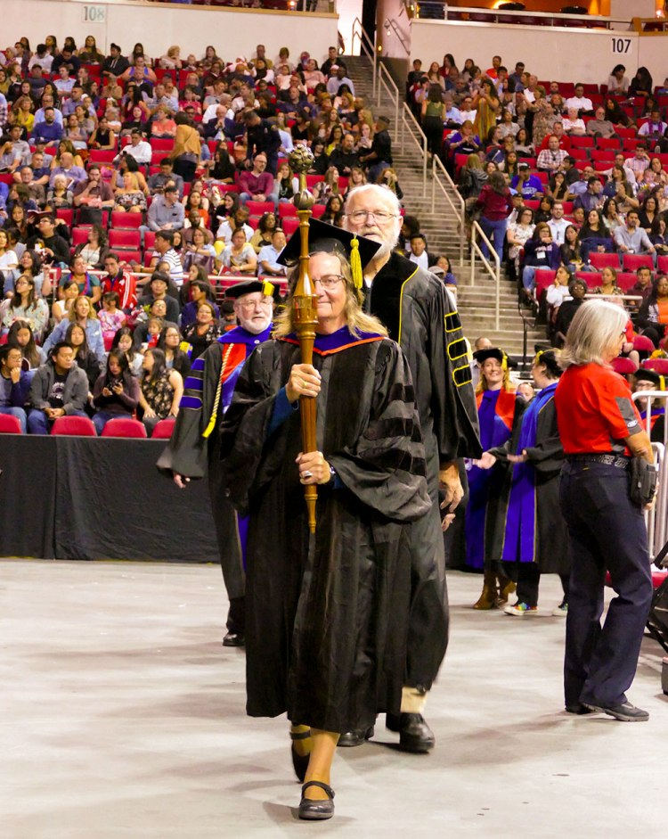 Bearing Fresno State's ceremonial mace, Chris Henson leads the faculty procession into the Save Mart Center for the University's 108th Commencement. (Photo: Benjamin Kirk/Fresno State)