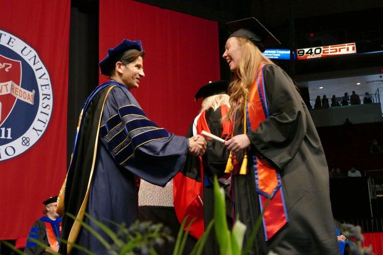 CAH graduate shakes Dr. Saúl Jiménez-Sandoval as she walks across the stage.