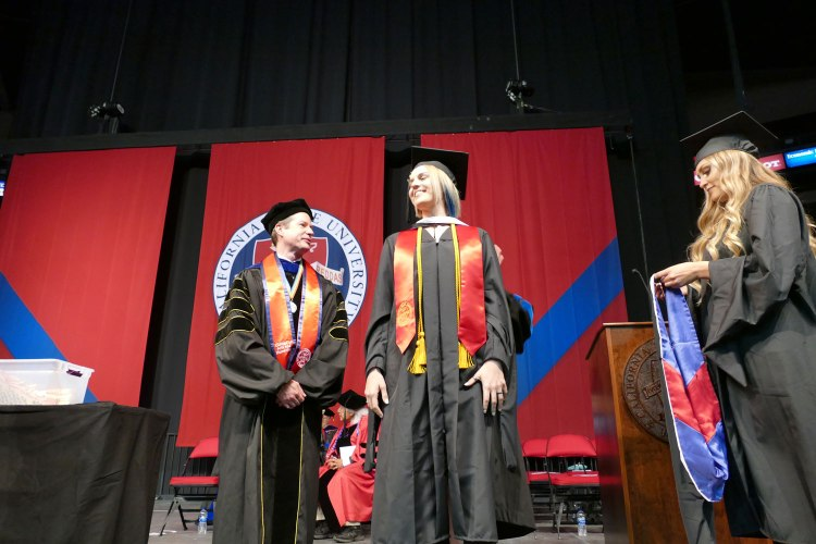 Alyssa Espinola receives her Master of Arts hood in Communication.