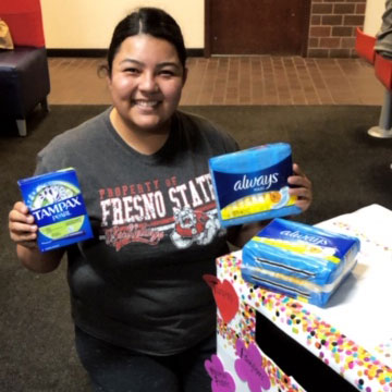 Student Giselle Hernandez hold mensuration products next to a donation bin.