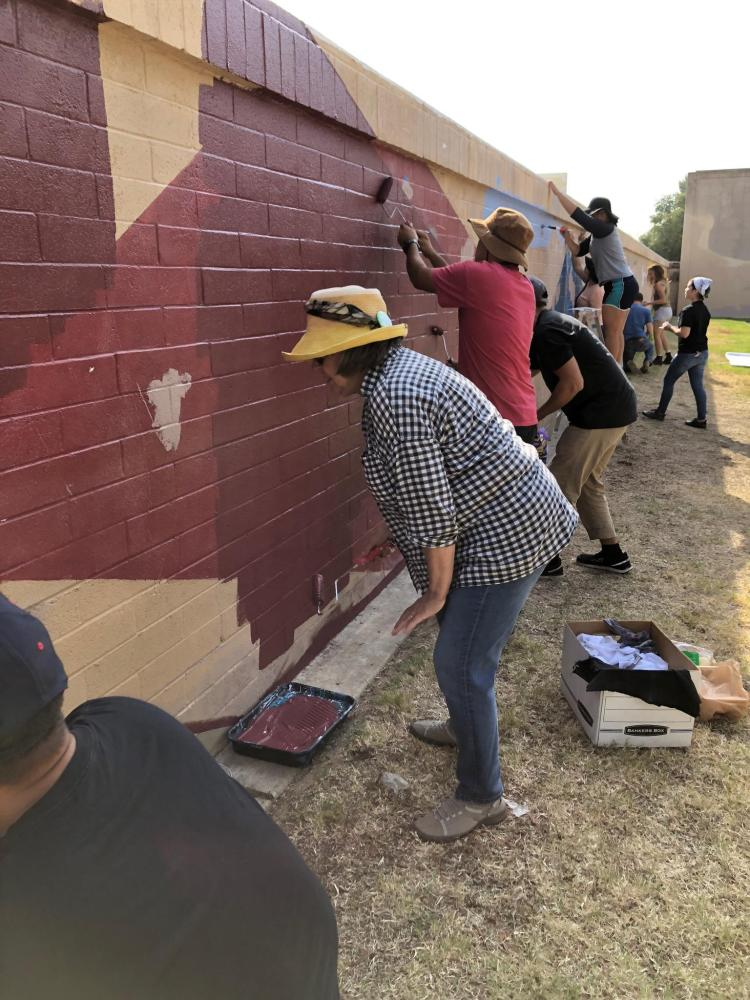 Students and volunteers work on the mural