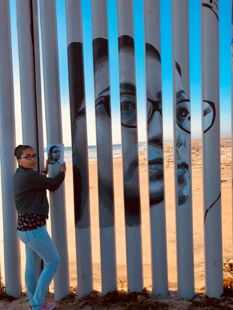 Tania stands by her image on the border wall.