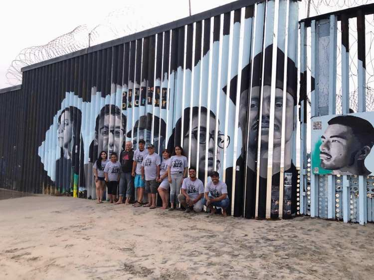 Lizbeth De La Cruz Santana and a group of volunteers pose at the Playas de Tijuana Mural Project