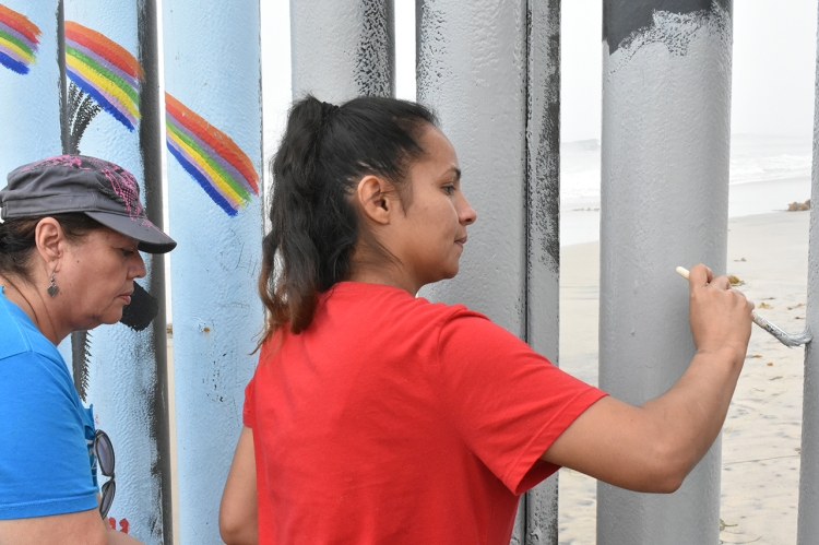 Volunteers paint the steel slats which make up the U.S.-Mexico border wall at Playas de Tijuana.