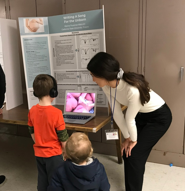 Marina Malcolm with two kids in front of her presentation