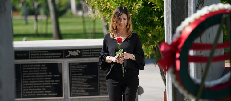 Vice President for Administration and Chief Financial Officer Deborah Adishian-Astone carries a rose to be laid in the Armenian Genocide Monument. Photo by Cary Edmondson.