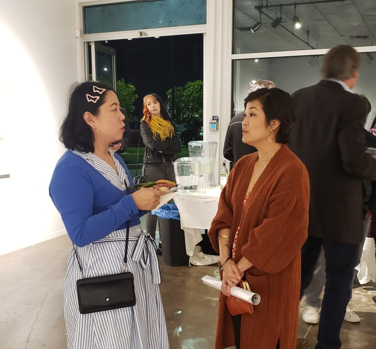 "Artist Phung Huynh (right) talks to a guest during the Arthop opening of her ""Resistance Aunties"" exhibition."