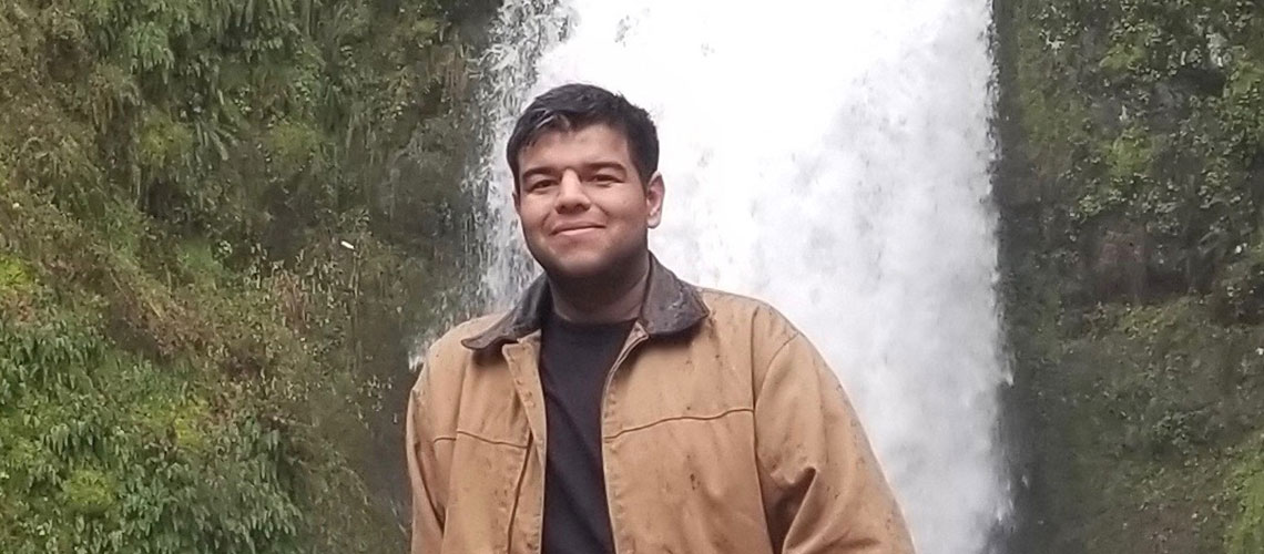 Olegario Tapia in front of a waterfall