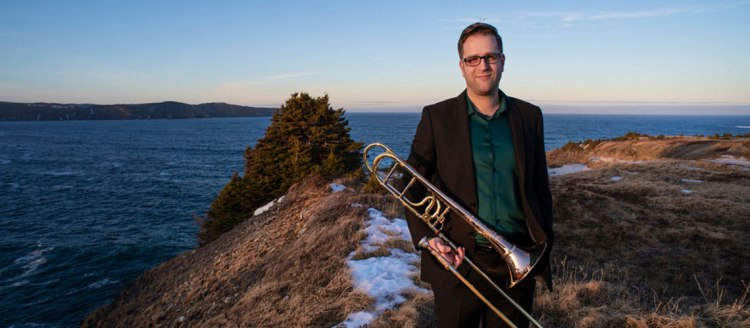 Dr. Stephen Ivany stands in front of an ocean bay holding his trombone.