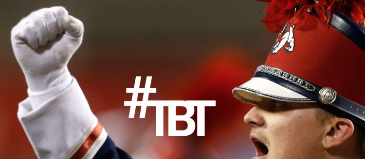 #TBT Throwback Thursday - Image of a Bulldog Marching Band Member in uniform holding his fist up.