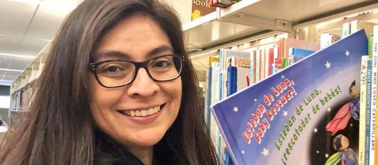 "Larissa Mercado-López holds her book ""Esteban de Luna, Baby Rescuer! / Esteban de Luna, ¡Rescatador de bebés!"""