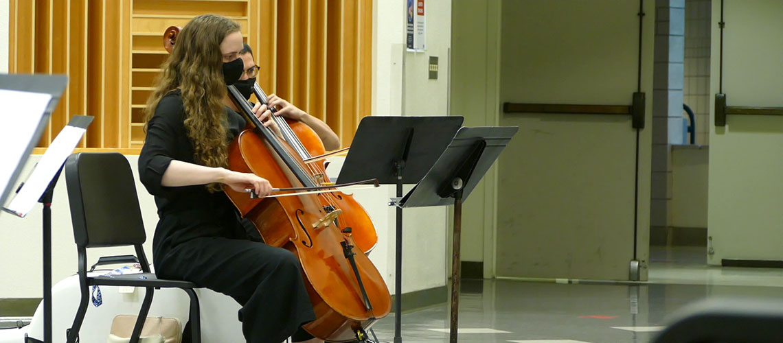 Amid COVID-19, Emma Hill plays the cello durning a live rehearsal in the band practice room.