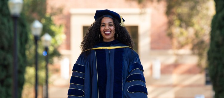 Alumna Kaelyn Rodríguez in her Ph.D. robes from UCLA.