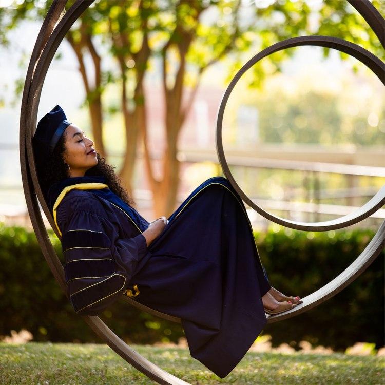 Alumna Kaelyn Rodríguez reclines inside a circular piece of outdoor art