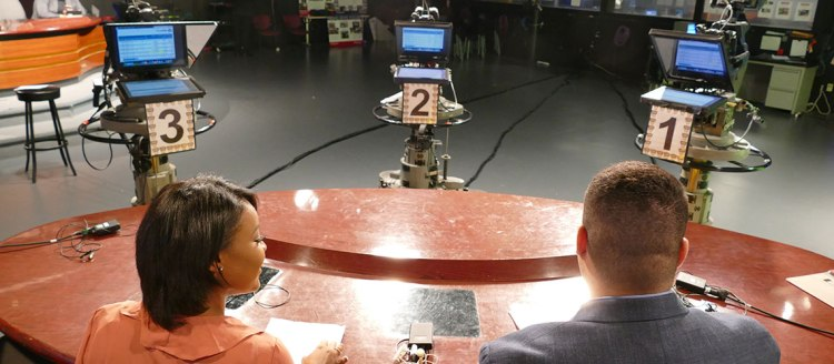 Two students looking into three cameras at the Fresno State Focus anchor desk in the Frenso State television studio.