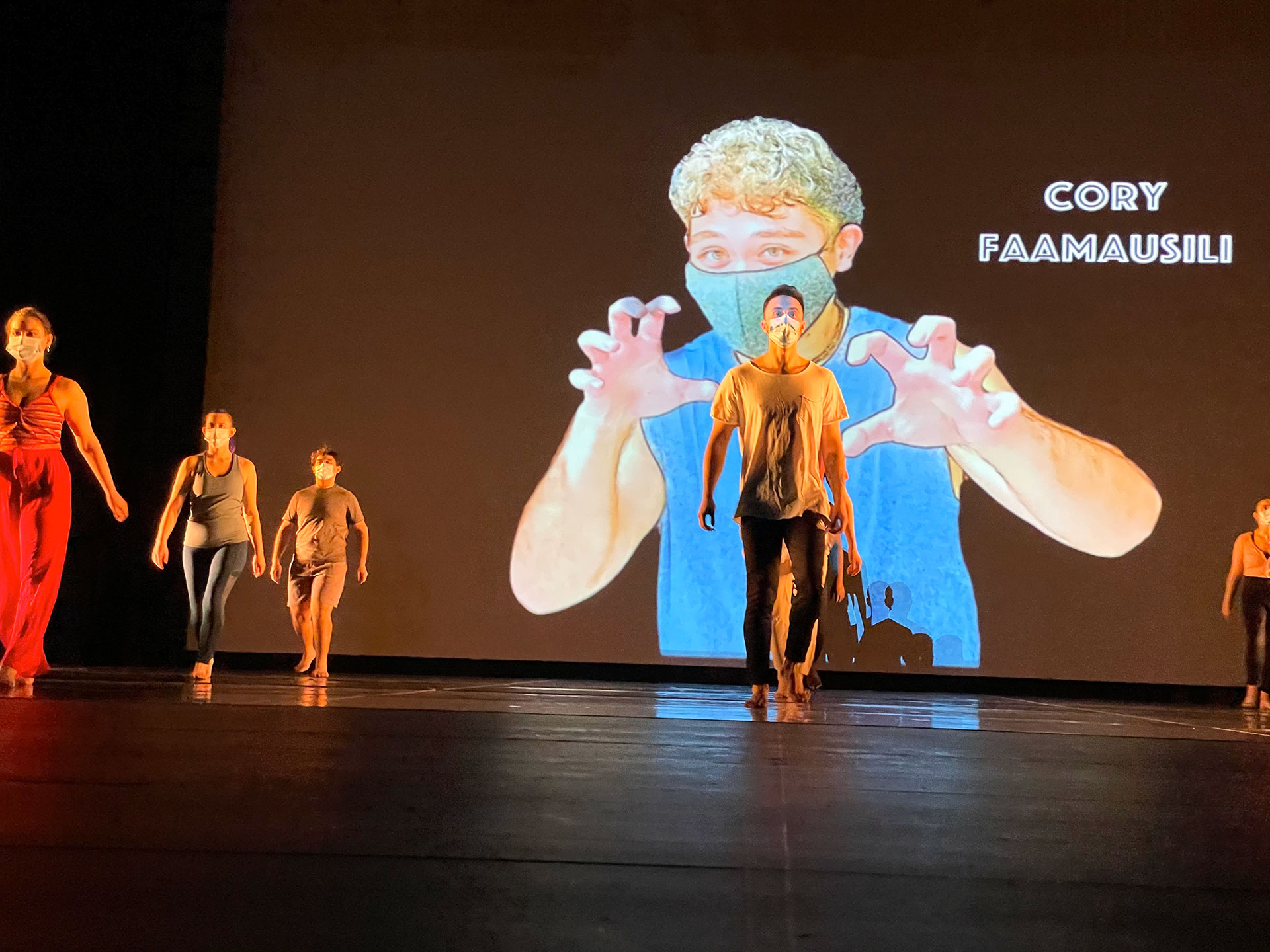 Dancers stand on stage with large image of dancer Cory Faamausili projected behind them.