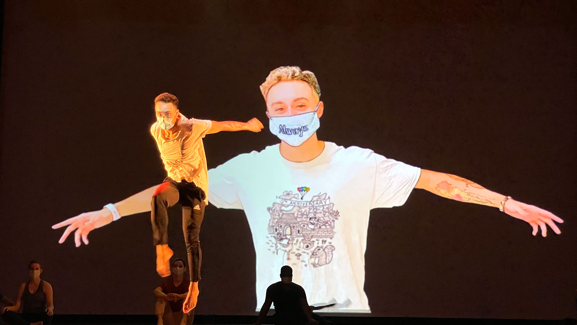 Solo dancer performs while large image of himself is projected behind him.