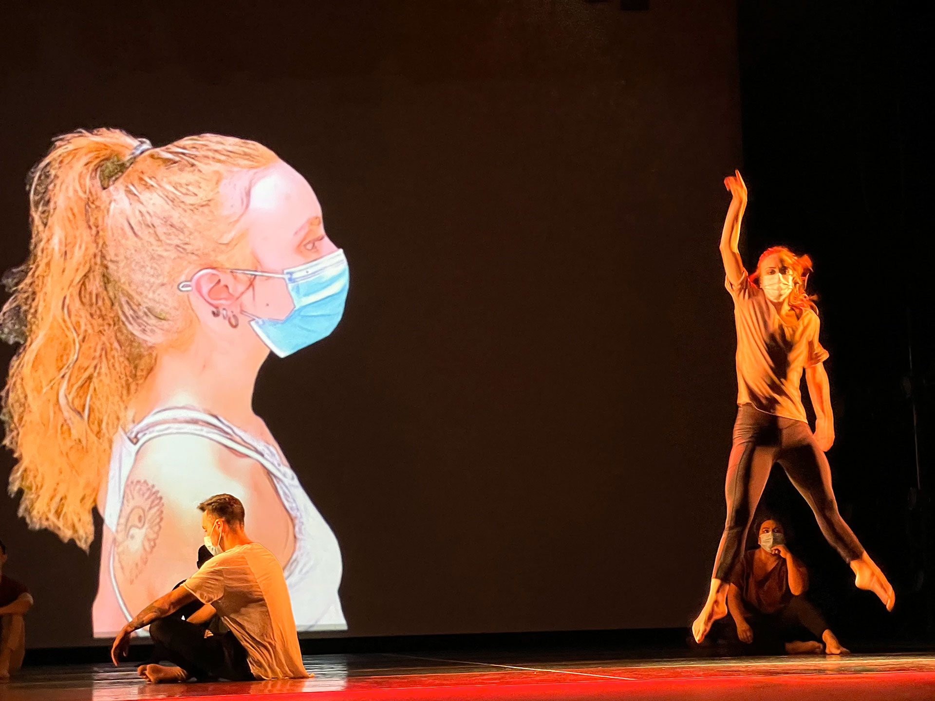 Solo dancer performs while large image of herself projected on the back of the stage looks over her.