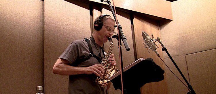 "Fresno State music theory and composition professor Benjamin Boone plays his alto saxophone in the studio while recording his album ""The Poets are Gathering."""