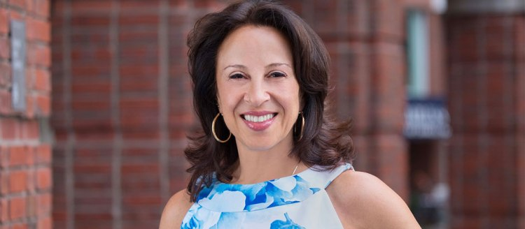 Maria Hinojosa in front of a brick building