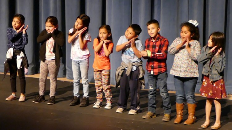 Young students perform on stage during Peach Blossom