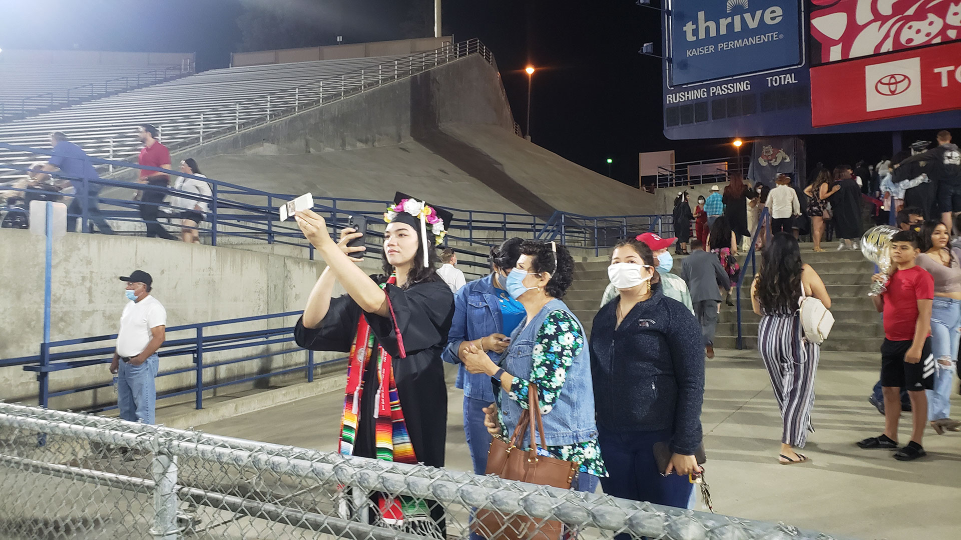 A student takes a selfie with loved ones after commencement.