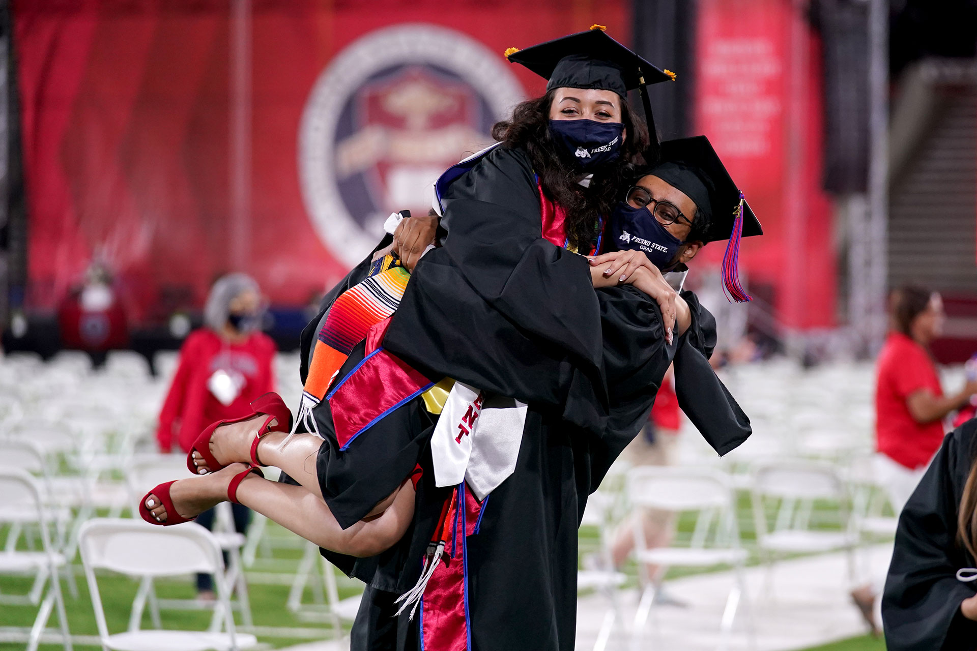 Two graduates hug each other.