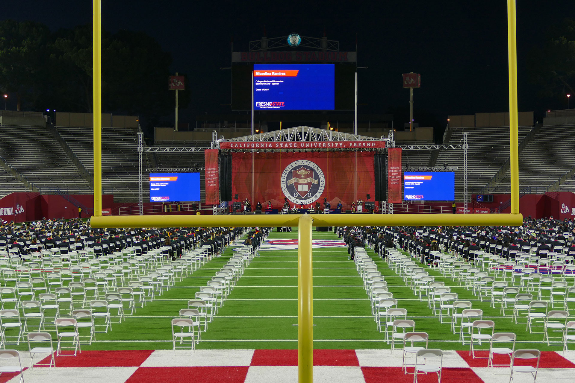 A view of the commencement ceremony through the football goal posts.