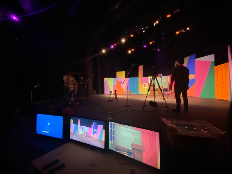 Monitors and camera's on a colorful stage set.