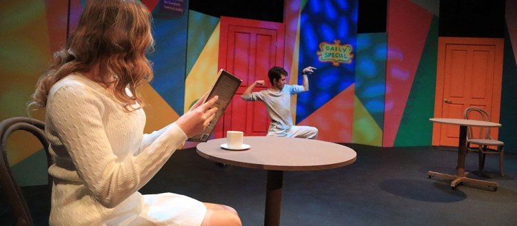 Woman holds a book with a cup of coffee while looking at a young man in a weird flex pose. All in front of an absurdly colorful background.