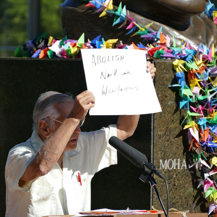 """Dr. Kapoor holds a hand-written sign which says """"Abolish Nuclear Weapons"""""""