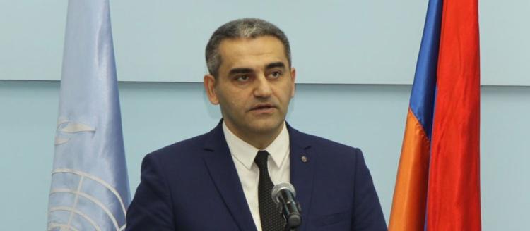 Dr. Suren Manukyan speaks next to the Armenian flag