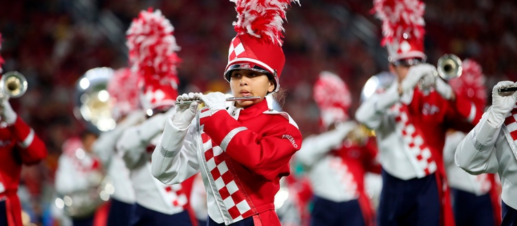 A Bulldog Marching band flute player is in focus with other band brass players blurred in the background as they perform in a stadium.