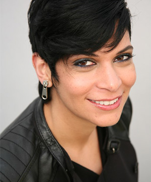 Headshot of Nassem Miller with a black leather top and zipper catch earrings.
