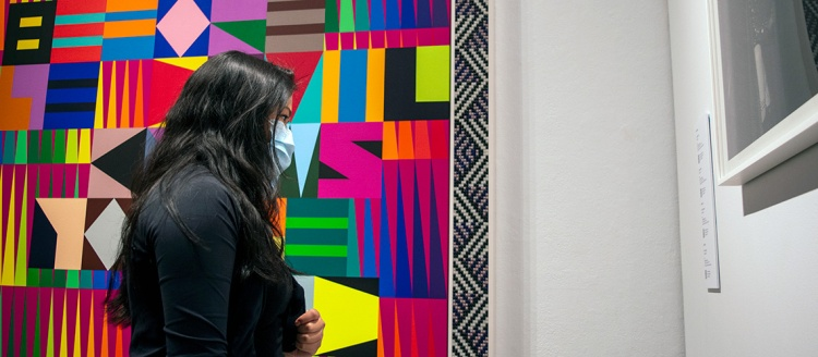 """English student Rachel Cruz tours the exhibition """"Nobody Promised You Tomorrow: Art 50 Years After Stonewall,"""" inside the Phebe Conley Art Gallery at Fresno State."""